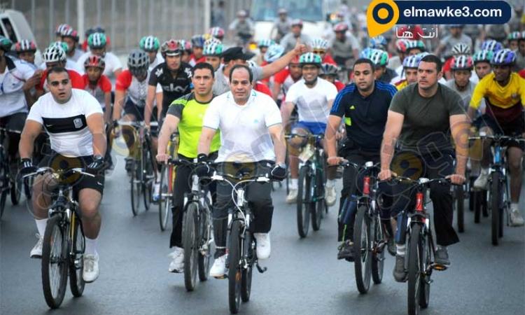 الرئيس السيسى يستقل دراجة ويسير بها وسط مجموعة من الشباب