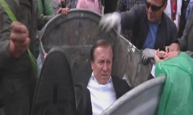 بالفيديو.. المتظاهرون في أوكرانيا يلقون نائب بالبرلمان في صندوق القمامة !!