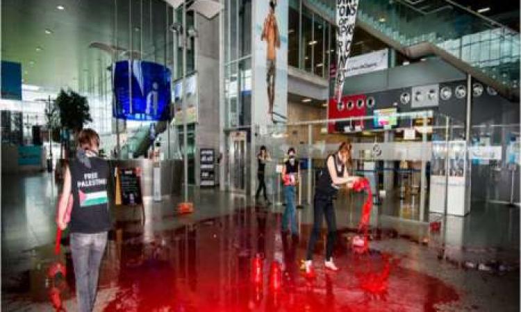 """بالصور .. ناشطات يغرقن مطارا بلجيكيا بالدماء.. """"أوقفوا تسليح إسرائيل"""""""