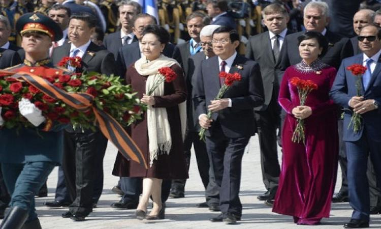 بالصور .. السيسى بباقة ورد يتصدر الصفوف الأولى باحتفالات روسيا