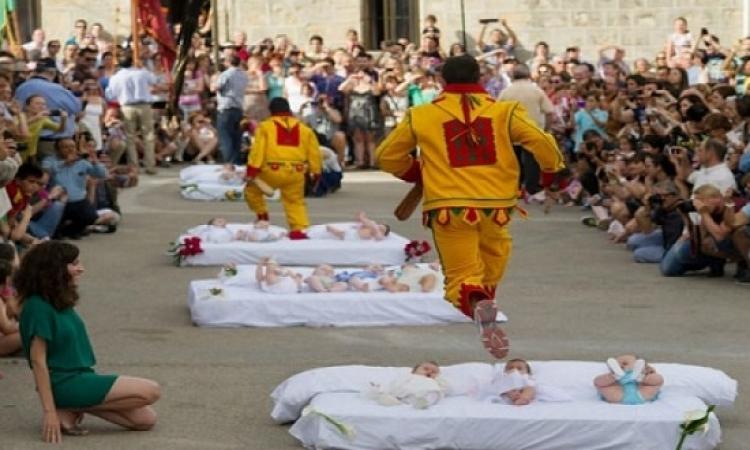 فى أسبانيا.. مهرجان القفز فوق الأطفال لتطهيرهم من الشرور !!