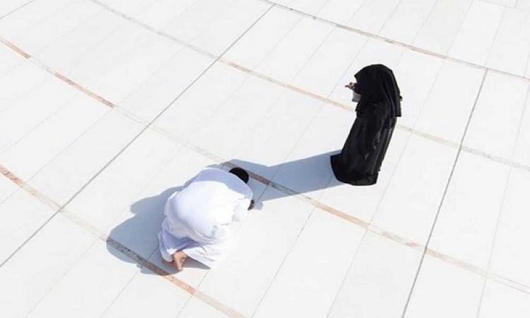 سعودى يصلى فى ظل زوجته بساحة الحرم المكى للوقاية من الشمس