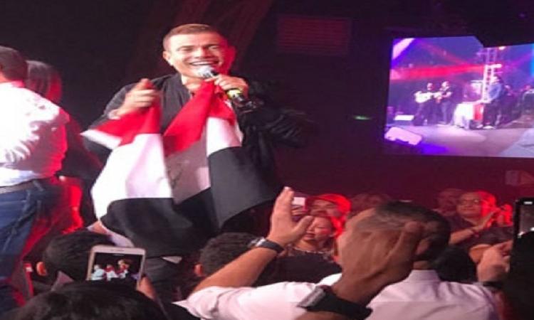 بالصور.. عمرو دياب يرفع علم مصر فى حفله بروسيا