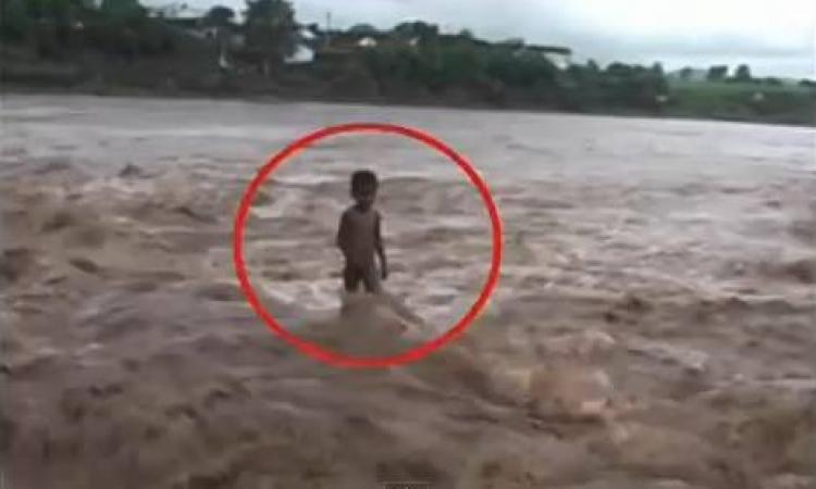 بالفيديو …طفل يقف على حافة فيضان مميت