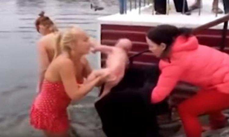 بالفيديو.. أم مجنونة ترضع طفلها فى بحيرة متجمدة