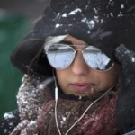 Woman crosses 1st Avenue as it snows in the Manhattan borough of New York