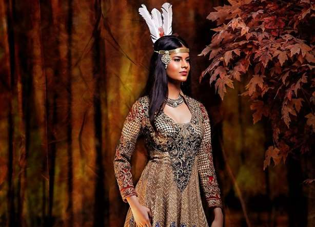بوكاهونتس بملابس هندية وزينة رأس مرصعة بالجواهر مع ثلاث ريش.