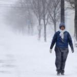 A woman walks through falling snow in New Haven