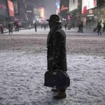 A man stands in falling snow on West 42nd street in Times Square in New York