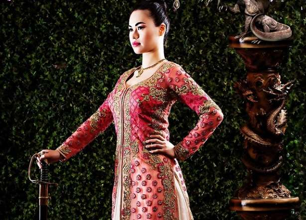 مولان بفستانٍ هندي مع سيف حقيقي وخلفية عشبية.