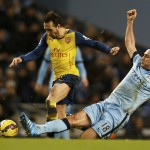 Arsenal's Santi Cazorla is challenged by Manchester City's Frank Lampard during their English Premier League soccer match at the Etihad stadium in Manchester