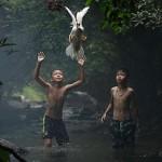 صبيان يحاول الامساك ببطلة وسط شلالات تايلاند