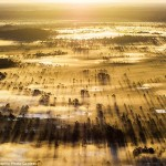 صورة تم التقاطها جوًا للضباب وهو ينشر موجاته  لتمتزج بأشعة الشمس لحظة الغروب