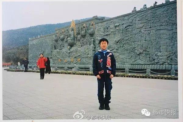 طفل بصورة تذكارية مع تمثال بوذا